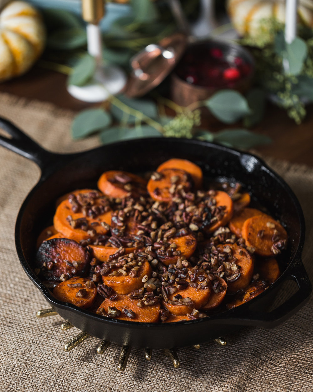 "Skillet Sweet Potatoes with Toasted Pecans - Yield: 6-8 servings1/2 cup light brown sugar1/4 cup granulated sugar1 teaspoon ground cinnamon1 teaspoon ground nutmeg1 pinch kosher salt1/2 cup unsalted butter6 sweet potatoes, peeled and sliced into 1/3"" rounds2 teaspoons vanilla extract3/4 cup pecans, chopped and toastedCombine the brown sugar, sugar, cinnamon, nutmeg and salt in a small bowl and set aside. In a large skillet or Dutch oven, melt the butter over medium heat. Add the sliced sweet potatoes and toss to coat with butter. Sprinkle the sugar mixture over the buttered potatoes and stir to coat. Reduce heat to low, cover skillet, and continue cooking for on ou; stirring occasionally. Once the sauce has caramelized the potatoes and they're fork-tender, stir in the vanilla. The sauce will thicken slightly once off the heat.In a separate sauté pan, toast the pecans before topping the candied sweet potatoes."