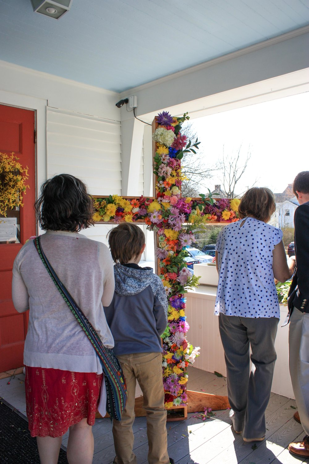 Church members added flowers to the cross that would be carried into the sanctuary during the service