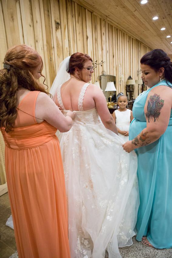 bridesmaid helping zip wedding dress