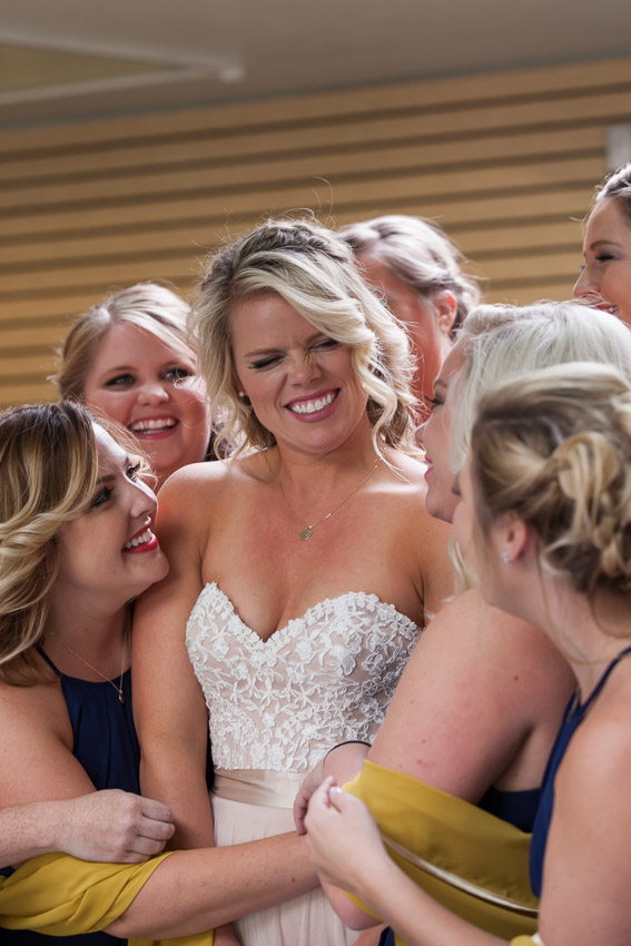 Bridesmaids give group hug to bride