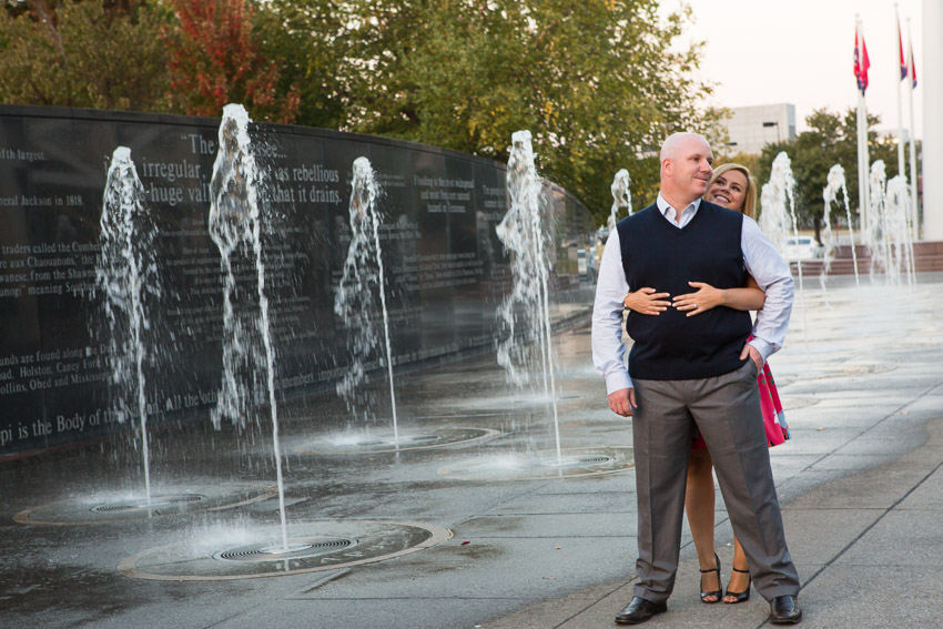 Fiance hugging by fountains