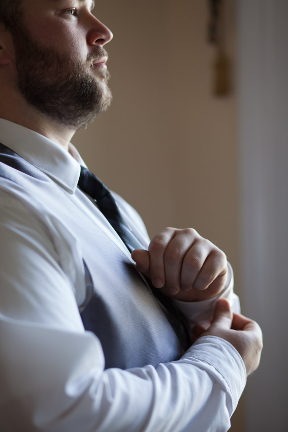 Groom getting dressed with cufflinks