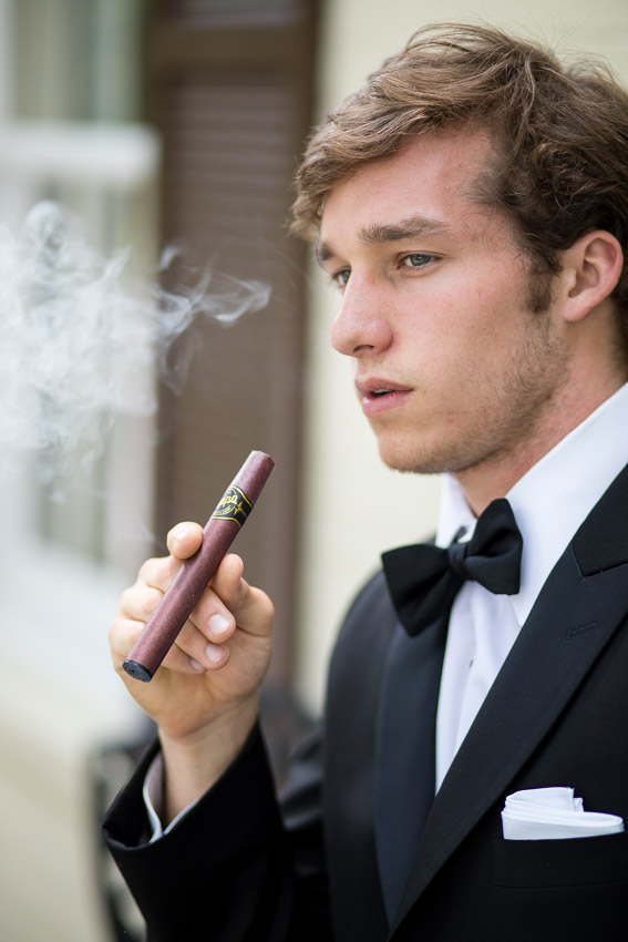 groom smoking cigar on wedding day