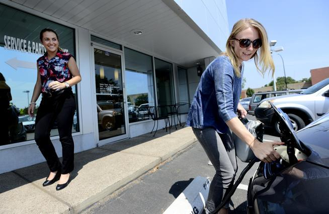 Michelle Daigle pulls the charging cord on her Nissan Leaf as Sara Cashin, Boulder Nissan's finance manager, looks on. (Paul Aiken / File photo)