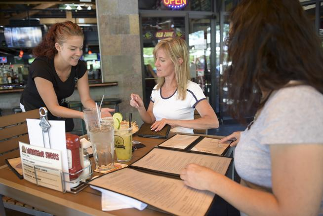 Dominique McKee delivers chips and salsa to Debbie Balsley, center, and Christine Wright at the Pumphouse Brewery & Restaurant, 540 Main St., Friday afternoon. (  Lewis Geyer / Staff Photographer  )