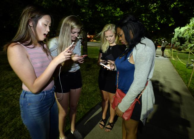 Megan Diller, Emma Dunder, Ashley Berg and Camile Clarke play Pokémon Go along with dozens of other players on a game hotspot on the University of Colorado Boulder Campus early Friday morning. (  Paul Aiken / Staff Photographer  )