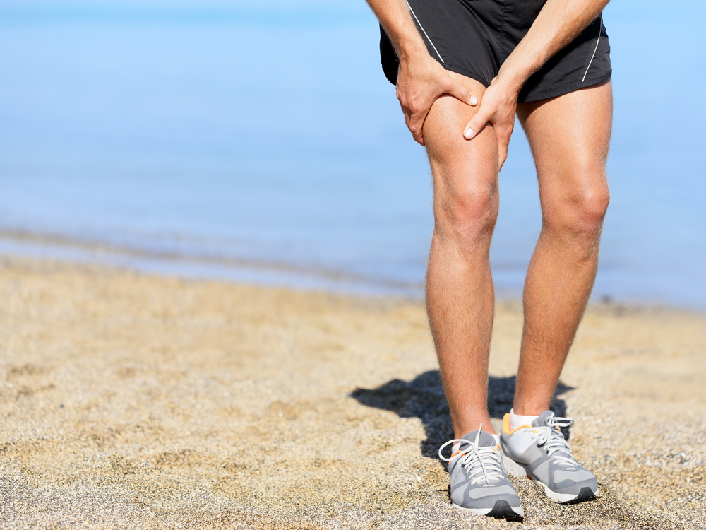 Man on beach in running shorts and shoes holding his thigh muscle