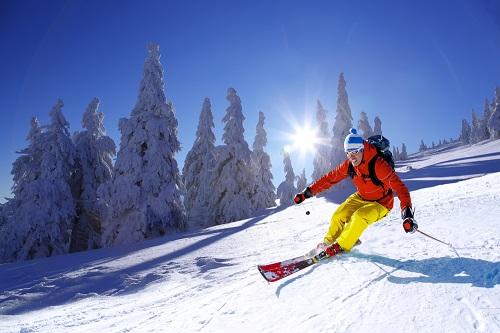 Man skiing down mountain in sunshine