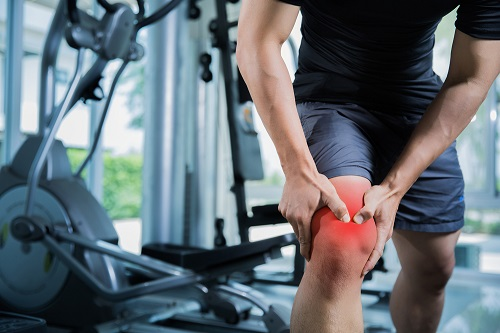 A man experiences knee pain at the gym
