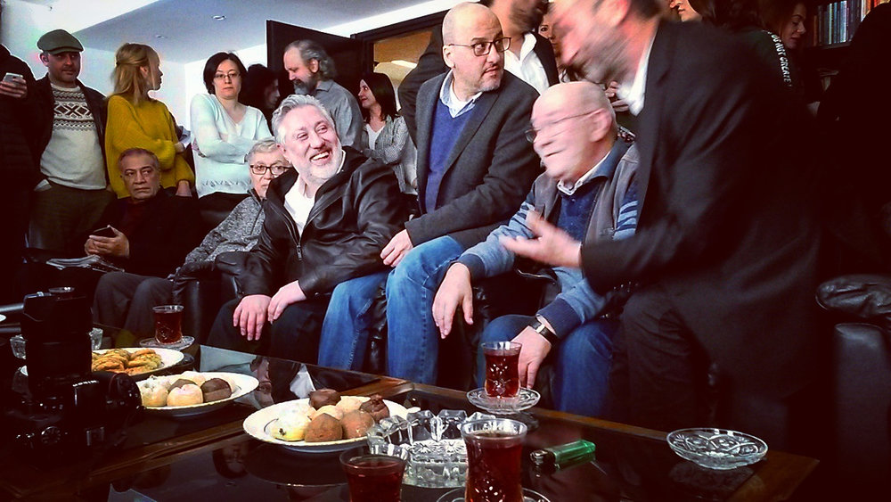 Murat Sabuncu (i skinnjacka), chefredaktör för tidningen Cumhuriyet, och grävreportern Ahmet Şık (sittande på soffkanten) firar att de har blivit villkorligt frigivna, mars 2018. Foto: Julie Honoré.