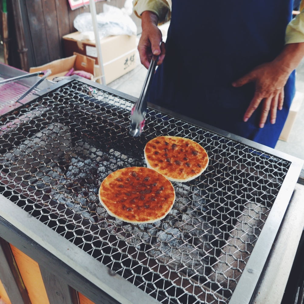 A street vendor grilling an osenbei (rice cracker).