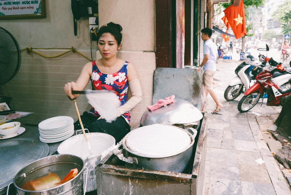 A street vendor prepares banh cuon.
