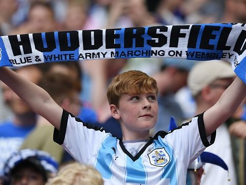 Huddersfield holds scarf aloft to celebrate the Terriers victory