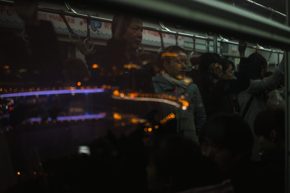 Commuters overlook the Jialing river, lit up at night with neon.  Chongqing, February 2017