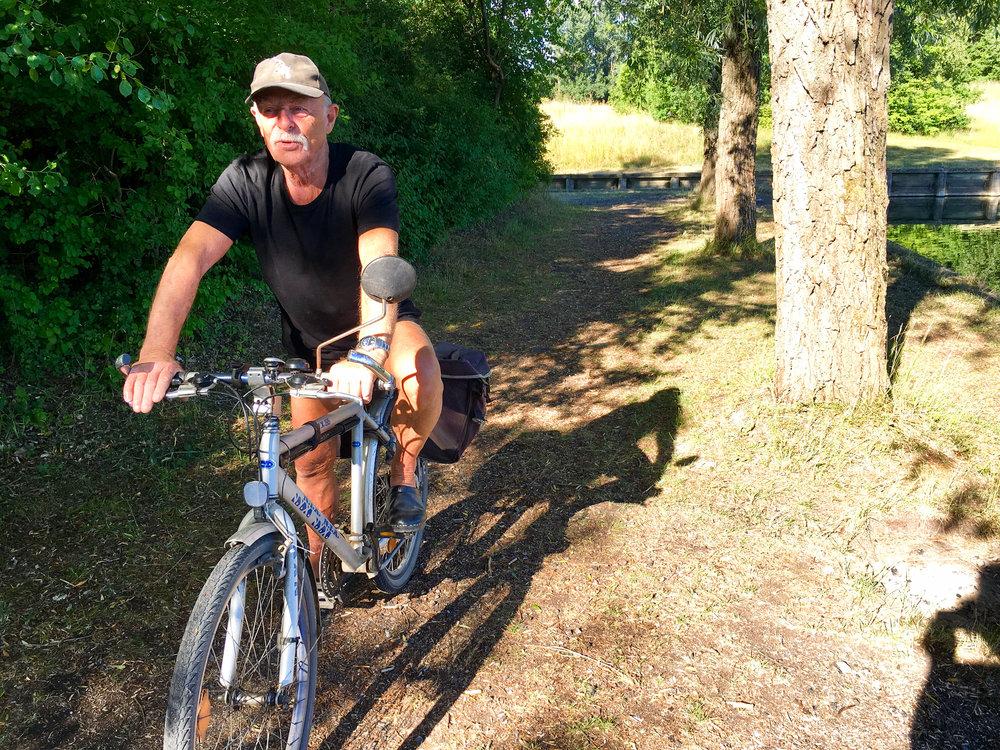 """Er du hjemløs? - Bill kommer cyklende mens jeg spiser morgenmad ved en sø. Han er 73, men kunne sagtens være 10 år yngre. Han har altid bevæget sig, holdt sig i gang. """"Skavanker skal gås væk,"""" lyder til at være hans motto. Faktisk har han rekorden i Bornholm Rundt, fortæller han. Tre dage tog det. Men andre har vist fået samme besked om at være rekordindehavere, griner han. Jeg fortæller om min tur over Danmark, og han mener, at der ikke er mange af min slags tilbage. """"Kom forbi til en øl og et hvil,"""" siger han. """"Jeg bor ved bageren."""""""