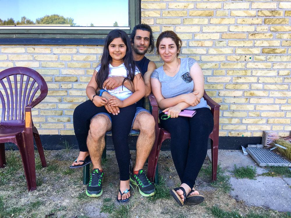 """Den bedste dag i lang tid - Jeg har kendt Sirwan siden 2015, da han kom med flygtningestrømmen til Danmark og ankom til teltlejren i Thisted. Han var altid meget hjælpsom i lejren, med det praktiske og med oversættelser. Han stod klar som den første og blev ved til det sidste, selv da han humpede rundt efter et vrid i knæet. Jeg har haft ham og en gruppe flygtninge ude at surfe i Klitmøller, og vi har snakket bjergbestigning og Mountain Medicine, som han er uddannet i. Der er dog ikke mange bjerge i Danmark, men til gengæld har han nået en endnu vigtigere top i sit liv. Sirwan har nemlig fået ophold og fået sin kone og datter til Danmark efter ikke at have set dem i fem år. Nu bor de sammen med omkring 100 andre i en isoleret flygtningeenklave, på værelser og i små lejligheder med fælleskøkken. Vi bager to plader med kanelsnegle og sætter os på plastikstolene ude foran. Alle der kommer forbi får en kanelsnegl. Børnene hjuler afsted på plastiktraktorer og løbecykler, mændene sætter sig i små grupper rundt omkring, ryger vandpipe og ser Youtube-videoer. Der skal ikke ske noget. Vi sidder bare i stolene, spiser og kigger. """"Det her er den bedste dag i lang tid,"""" er der en der siger."""