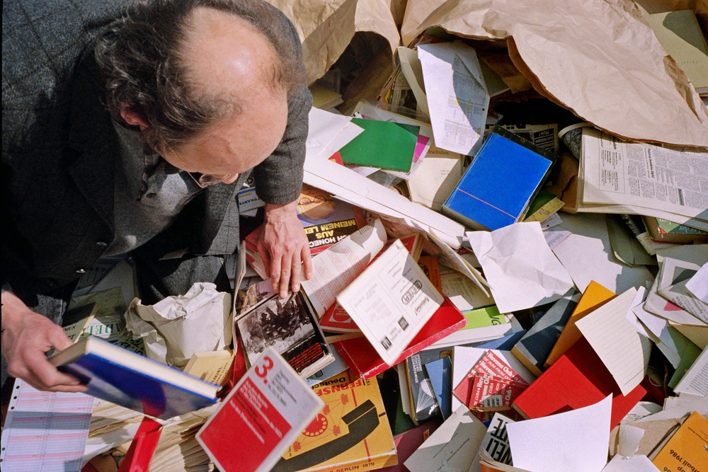 "My friend David was a ""junk remover"" permitted onto the Stasi headquarters at 15 Normanenstrasse and I accompanied him as an assistant with a camera. This image shows David knee deep in a dumpster full of bureaucratic junk, forms, photographs and a wealth of other interesting things."