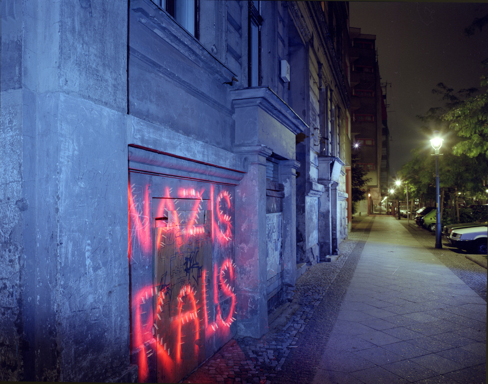 "A dramatization of a commonly seen bit of grafitti, grafitti seemed to be a blood sport and there was very little ""Art""  graffitti to be seen. It was always about territory and politics andvile nationalistic messages were common (Auslander Raus - foreigners out!)"