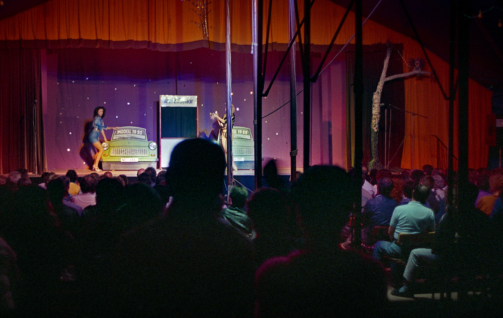 "A satirical burlesque comedy show in a tent near the Sport Stadion. The skit was based on the 1990 Trabi versus the 1969 Trabi - lots of new features eh? Exactly the same car- but that is progress in the DDR - that was the joke. Dark in there. Berlin 1990.         Normal   0           false   false   false     EN-CA   X-NONE   X-NONE                                                                                                                                                                                                                                                                                                                                                                                                                                                                                                                                                                                                                                                                                                                                                                                                                                                                   /* Style Definitions */  table.MsoNormalTable 	{mso-style-name:""Table Normal""; 	mso-tstyle-rowband-size:0; 	mso-tstyle-colband-size:0; 	mso-style-noshow:yes; 	mso-style-priority:99; 	mso-style-parent:""""; 	mso-padding-alt:0cm 5.4pt 0cm 5.4pt; 	mso-para-margin-top:0cm; 	mso-para-margin-right:0cm; 	mso-para-margin-bottom:8.0pt; 	mso-para-margin-left:0cm; 	line-height:107%; 	mso-pagination:widow-orphan; 	font-size:11.0pt; 	font-family:""Calibri"",sans-serif; 	mso-ascii-font-family:Calibri; 	mso-ascii-theme-font:minor-latin; 	mso-hansi-font-family:Calibri; 	mso-hansi-theme-font:minor-latin; 	mso-fareast-language:EN-US;}"