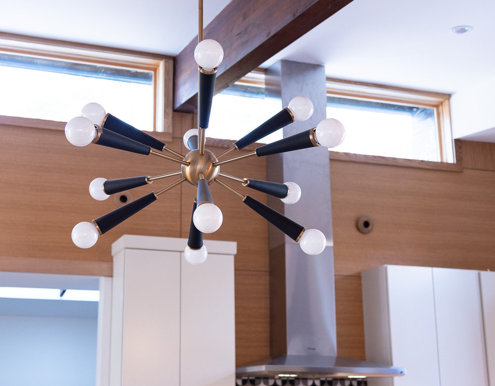 A fun and modern light fixture hangs over the island in the kitchen