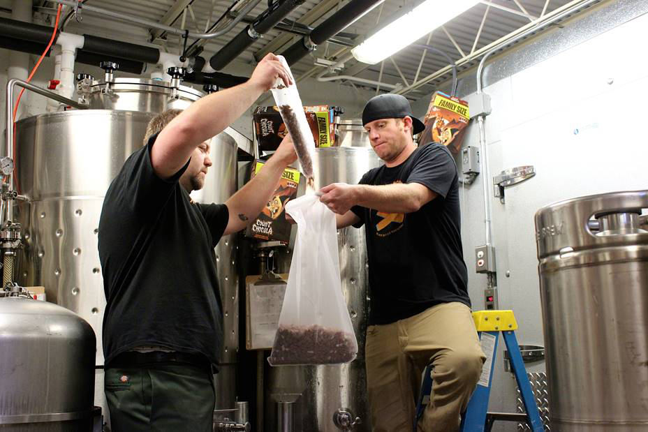 Photo: Black Bottle Brewery Black Bottle Brewery Head Brewer Tom Moseman and owner Sean Nook pour some Count Chocula cereal into a batch of their Cerealiously beer.
