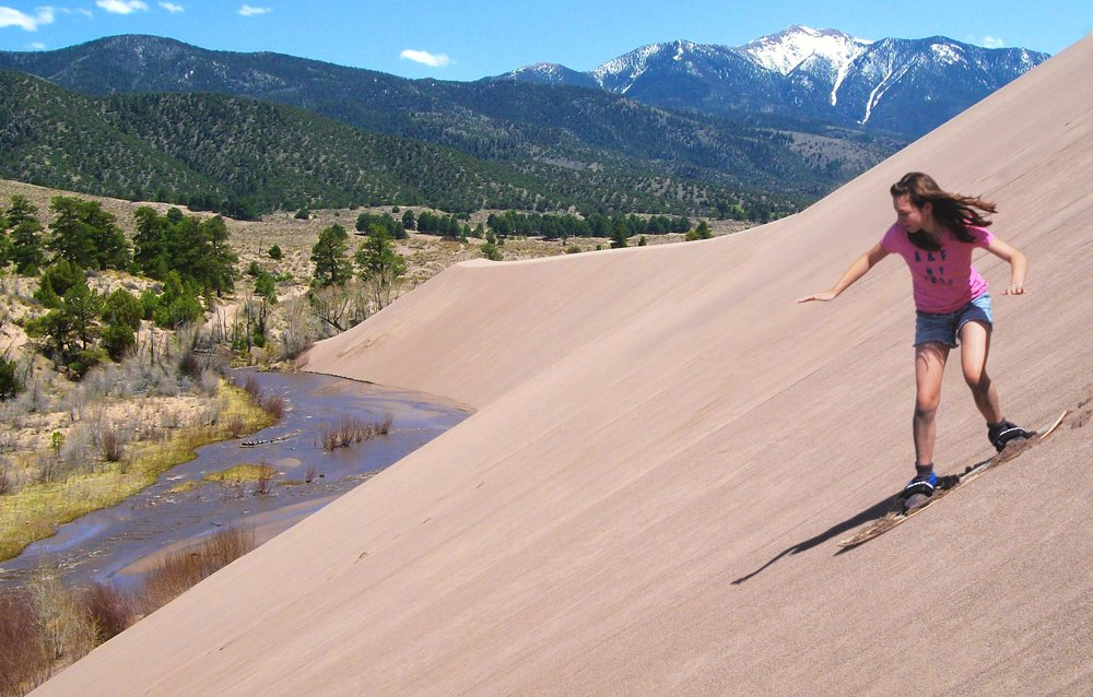 Girl Sandboarding Above Medano Creek, Castle Creek Picnic Area by NPS/Patrick Myers, is licensed under CC BY 2.0
