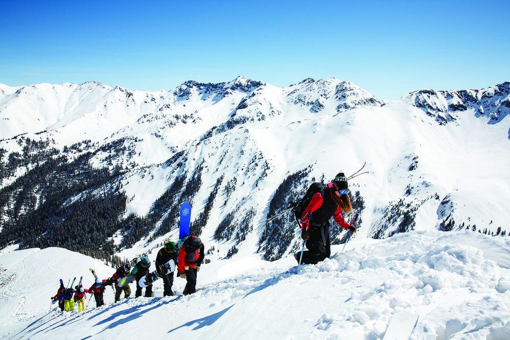 skiers ascend the ridgeline to higher terrain on Silverton Mountain.