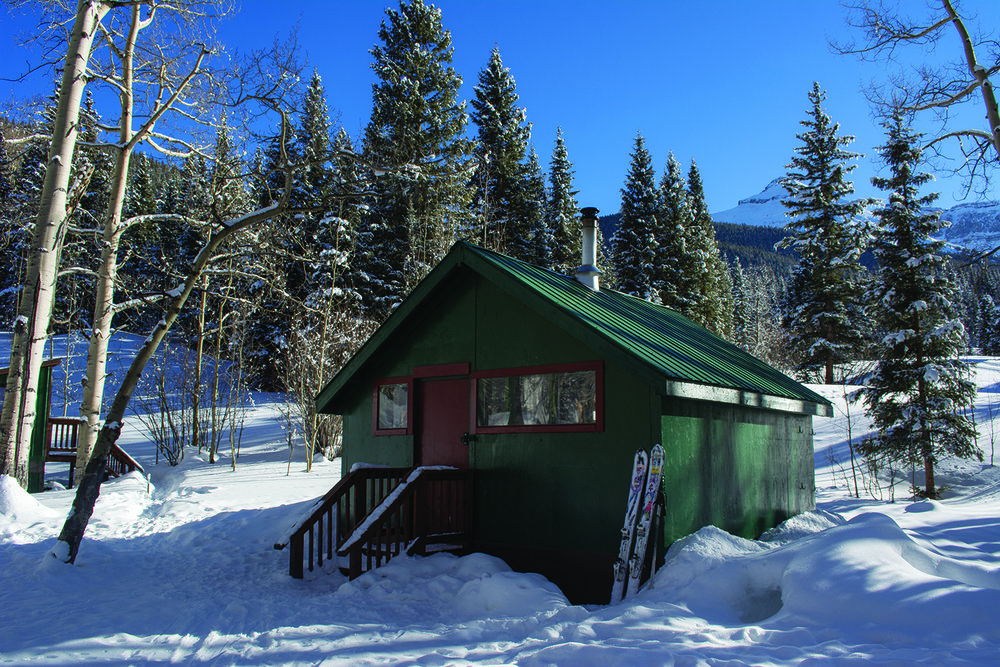 The Burn Hut is nestled in a grouping of aspen and pine trees beneath Whitehouse Mountain.