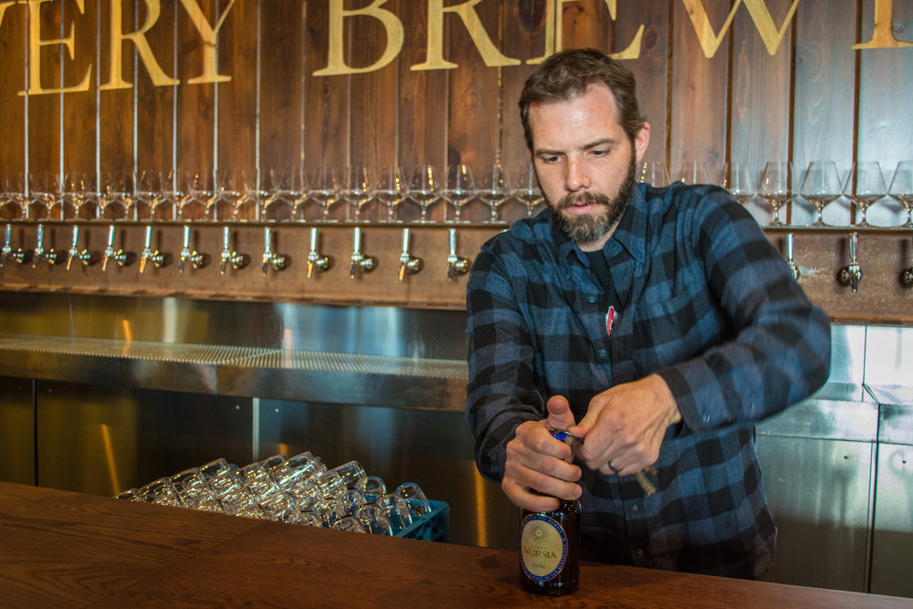 Travis Rupp cracks open a Nursia brew that he bottled with the Umbrian monks who crafted it.
