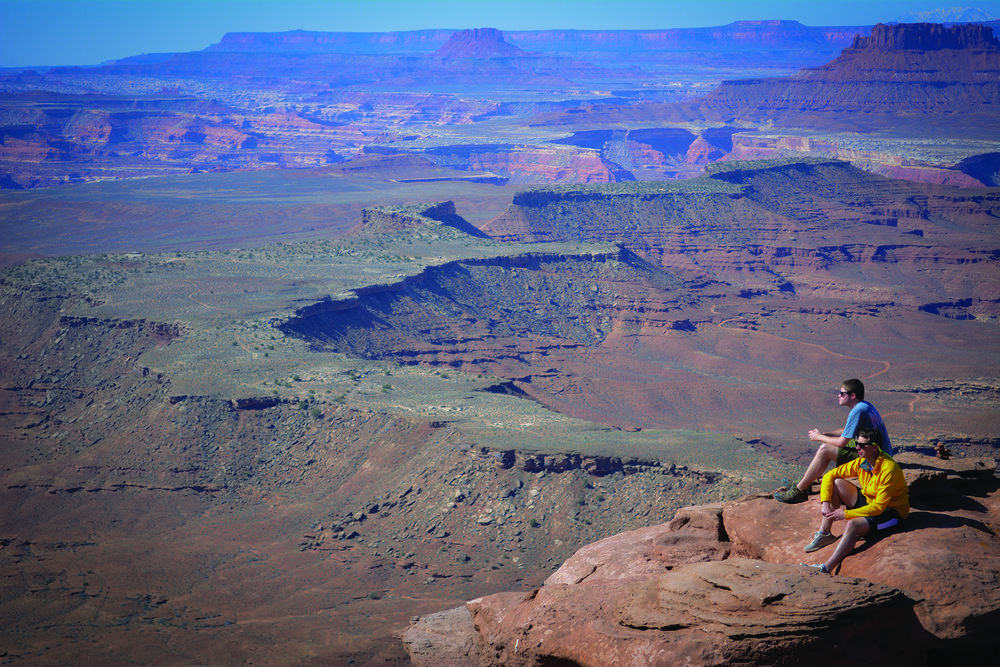 Hikers overlook Canyonlands National Park from Murphy Point at Island In The Sky. Photo Neill Pieper