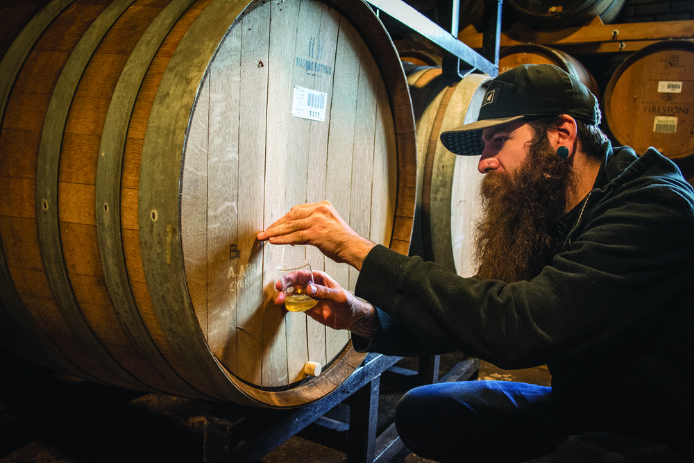 Joshua Safer pulls a nail to sample a beer that's been aging for three years.