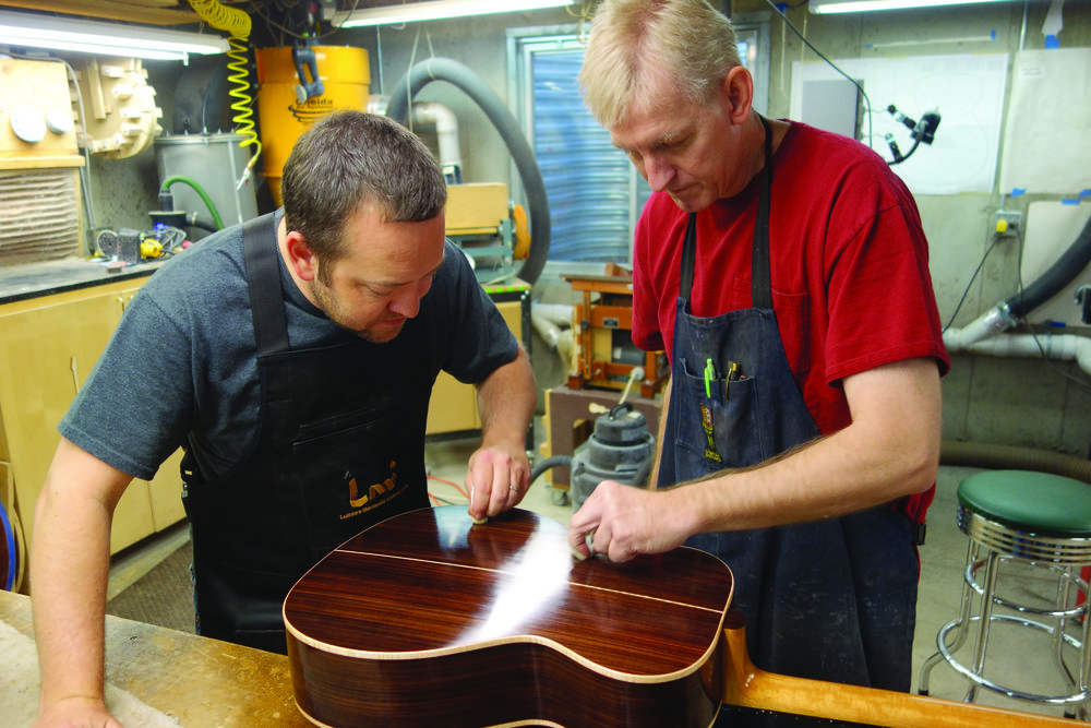 Robbie O'Brien, right, works with a student during a guitar building class. Photo courtesy of Robbie O'Brien at O'Brien Guitars.