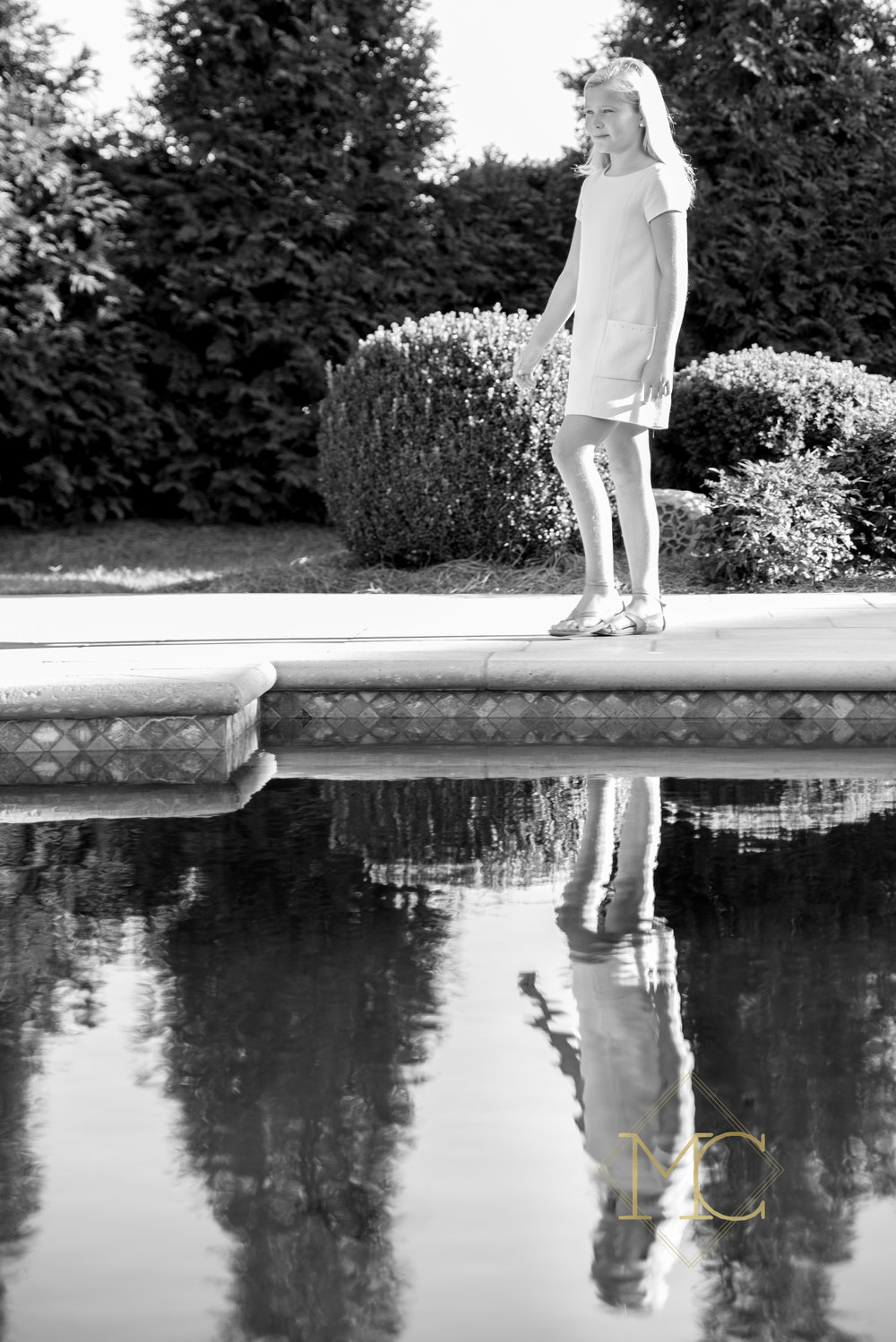 image from a fall session of a tween girl walking by a pool
