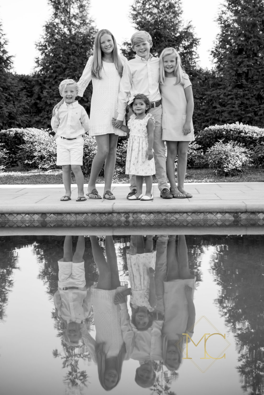 image from a fall session of five cousins standing by a pool
