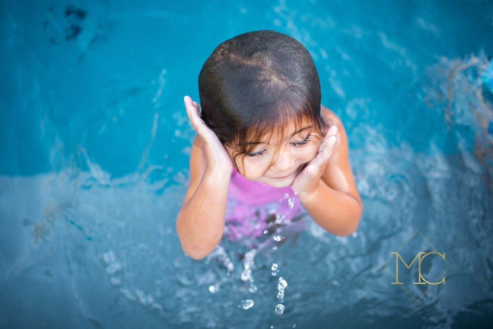image from a fall session shooting down towards a little girl getting out of a pool