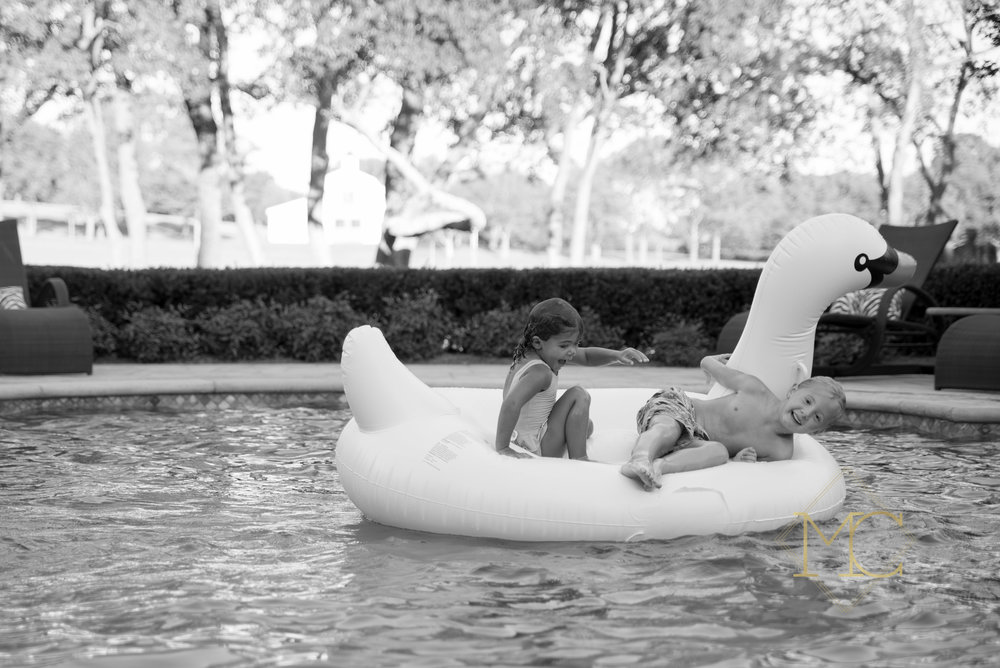 image from a fall session of a boy and girl playing on a swan