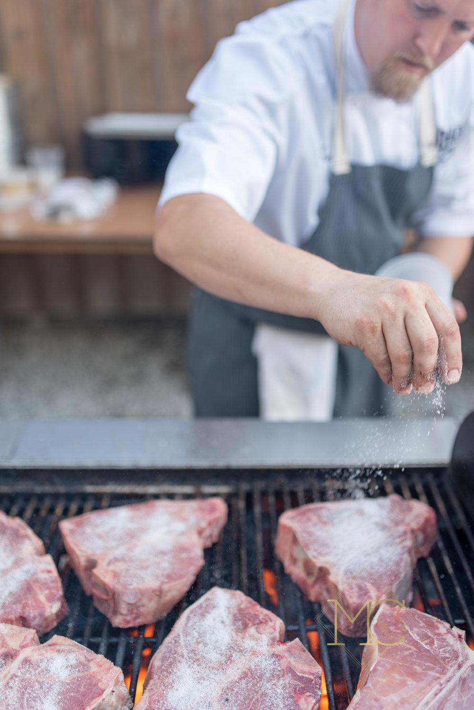 image from multiple sclerosis event of chef eric zizka of oak steakhouse nashville preparing steaks