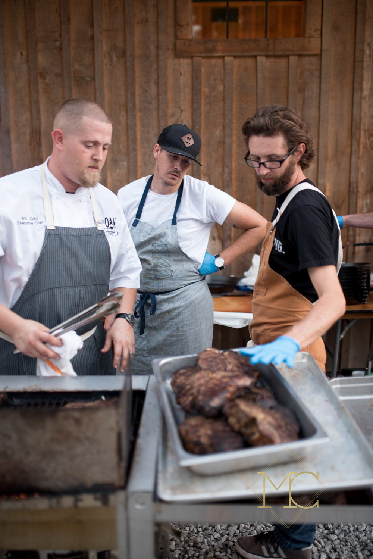 image from multiple sclerosis nashville event of chef trey cioccia of the farm house nashville, travis mcshane of adele's nashville, and eric zizka of oak steakhouse nashville over steaks