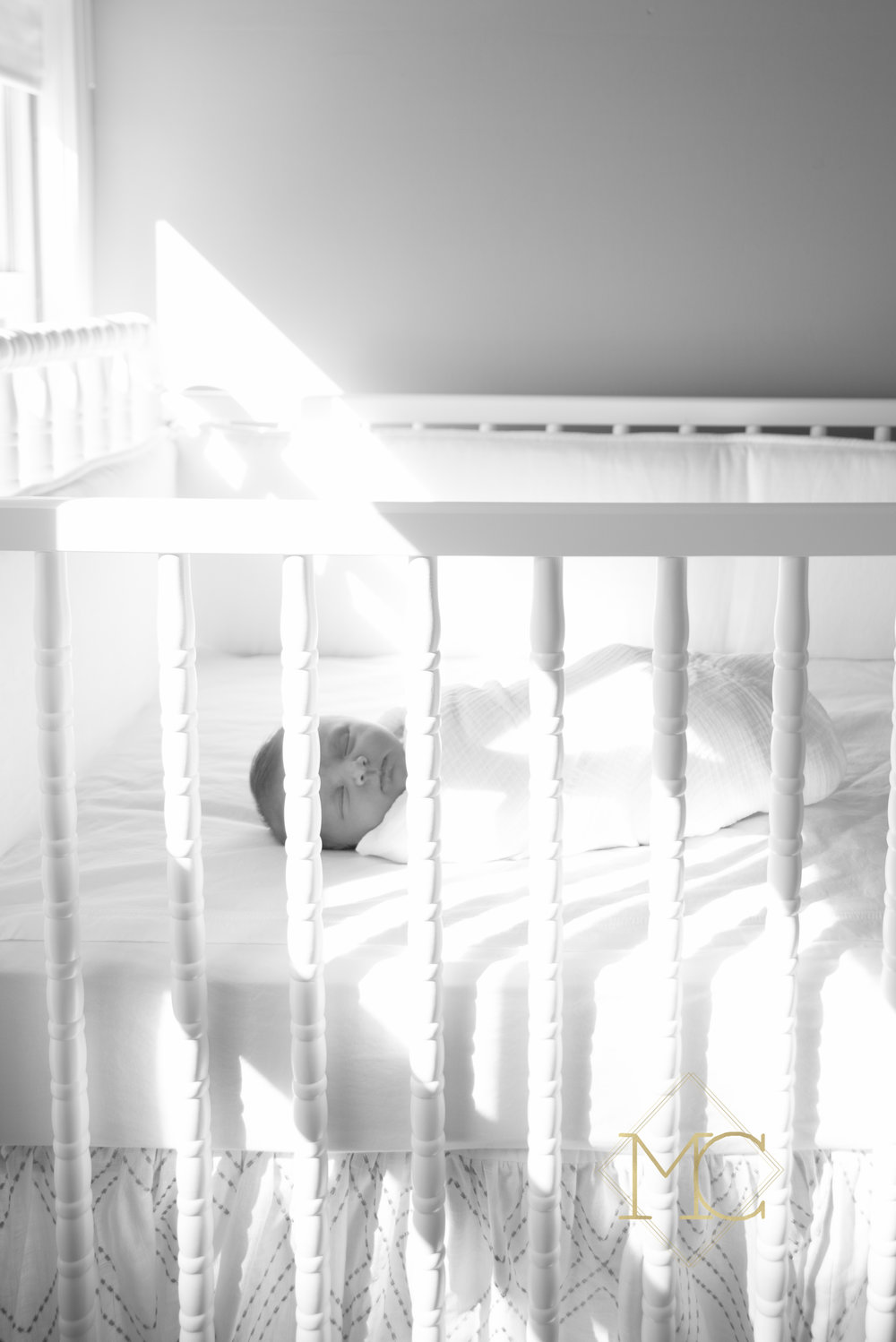 image from nashville newborn lifestyle photo session of baby swaddled in her crib