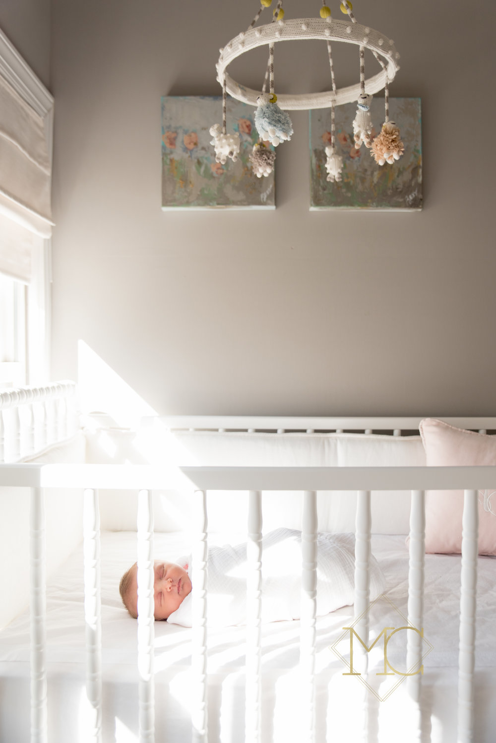 image from nashville newborn lifestyle photo session of baby girl in her nursery with art and mobile