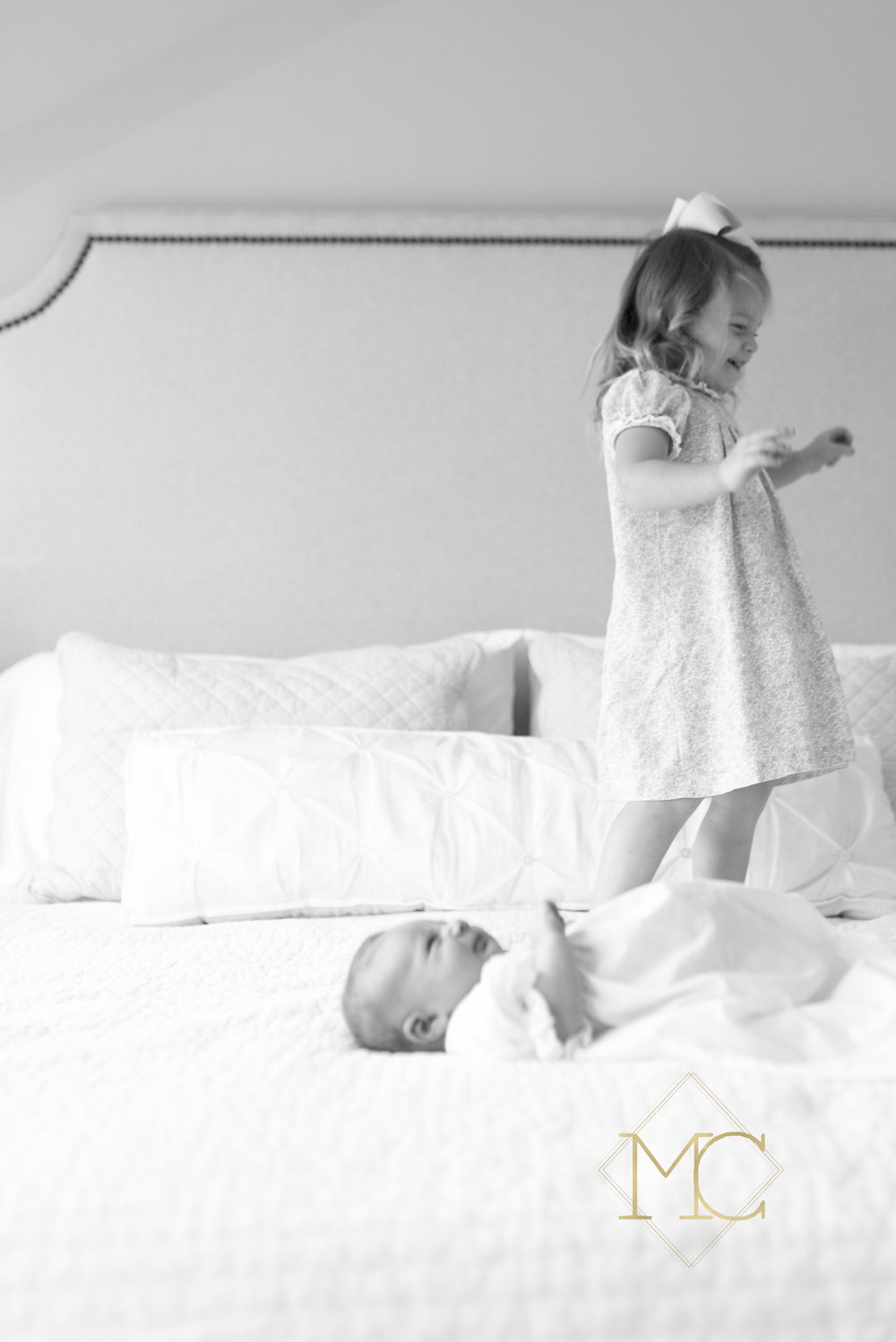image from nashville newborn lifestyle photo session of big sister jumping on the bed with baby