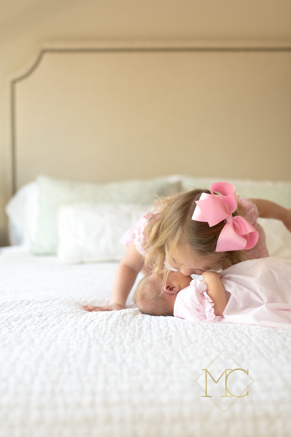 image from nashville newborn lifestyle photo session of big sister kissing baby