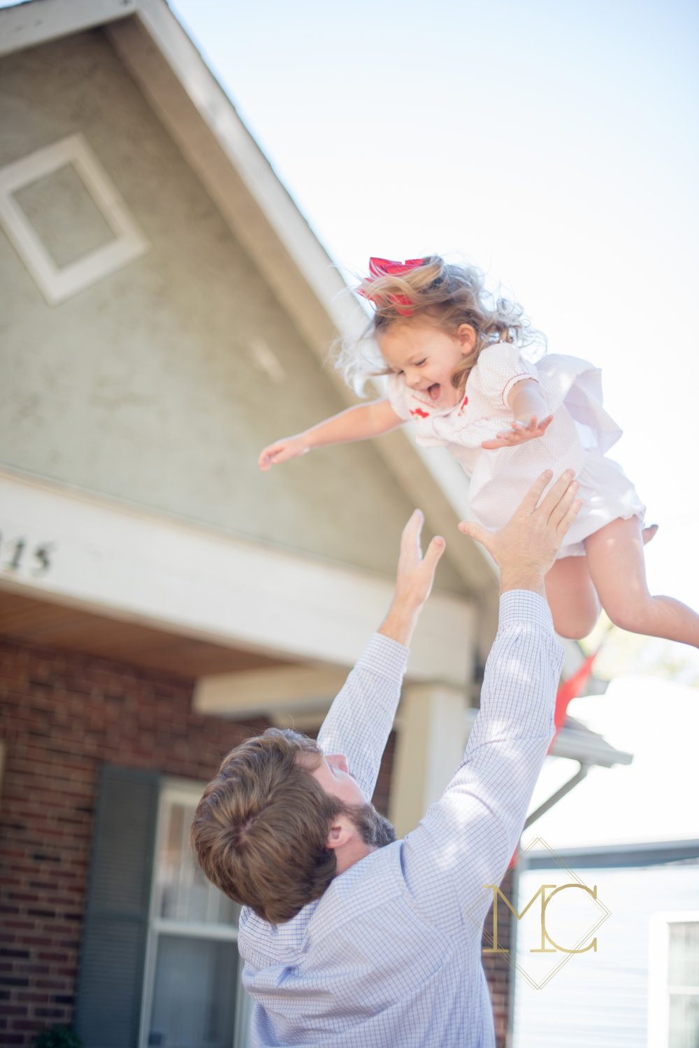 image from nashville family lifestyle photo session of dad throwing toddler in the air