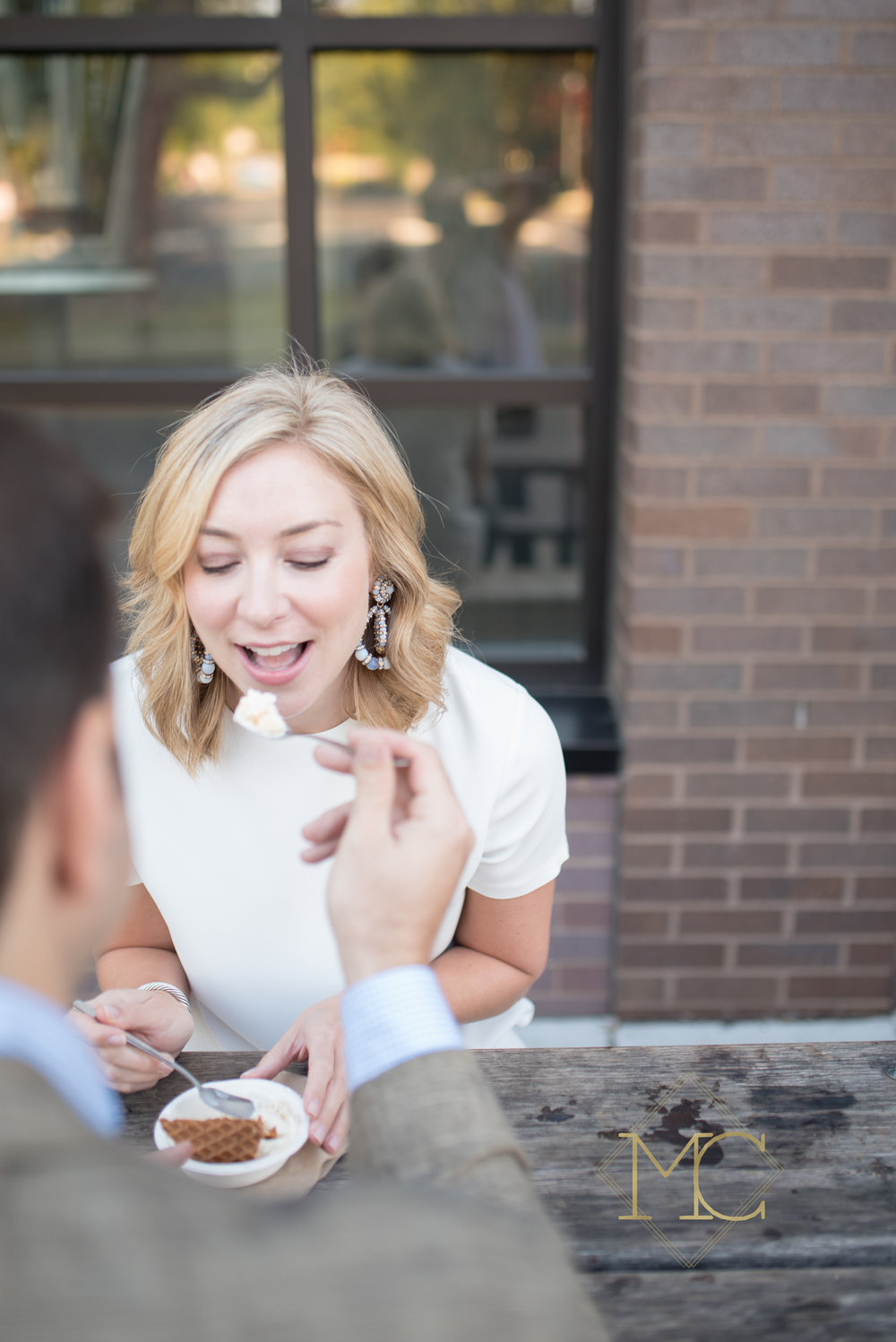image from nashville engagement photo session of couple eating ice cream at jeni's ice cream in 12 south