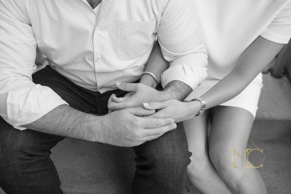 image from nashville engagement photo session of a couple in love at jeni's cream in 12 south holding hands, engagement ring