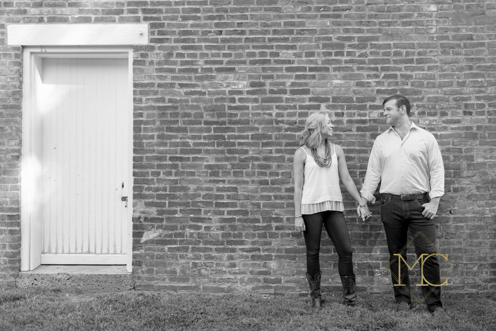 image from nashville engagement photo shoot of couple at glen leven farm walking in the woods by barn