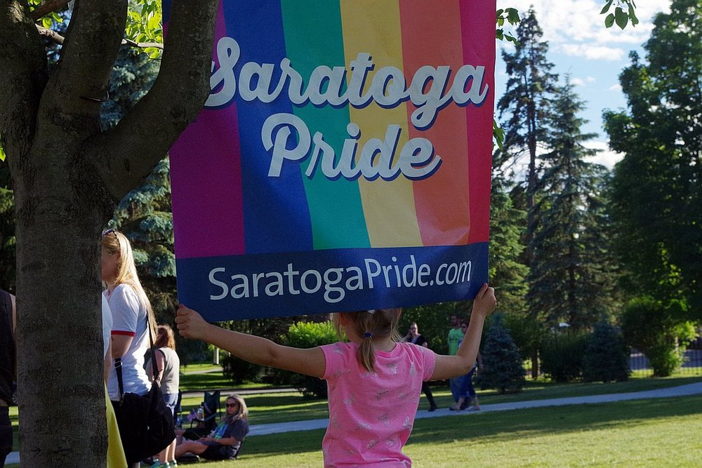 Sophie Smemo, 6, of Wilton, holds onto the Saratoga Pride sign hanging at Congress Park in downtown Saratoga during a vigil being held for the victims of the Pulse LGBTQ nightculb shooting in Orlando this past weekend, on Tuesday June 14, 2016  |  PHOTO: Ryan Zidek