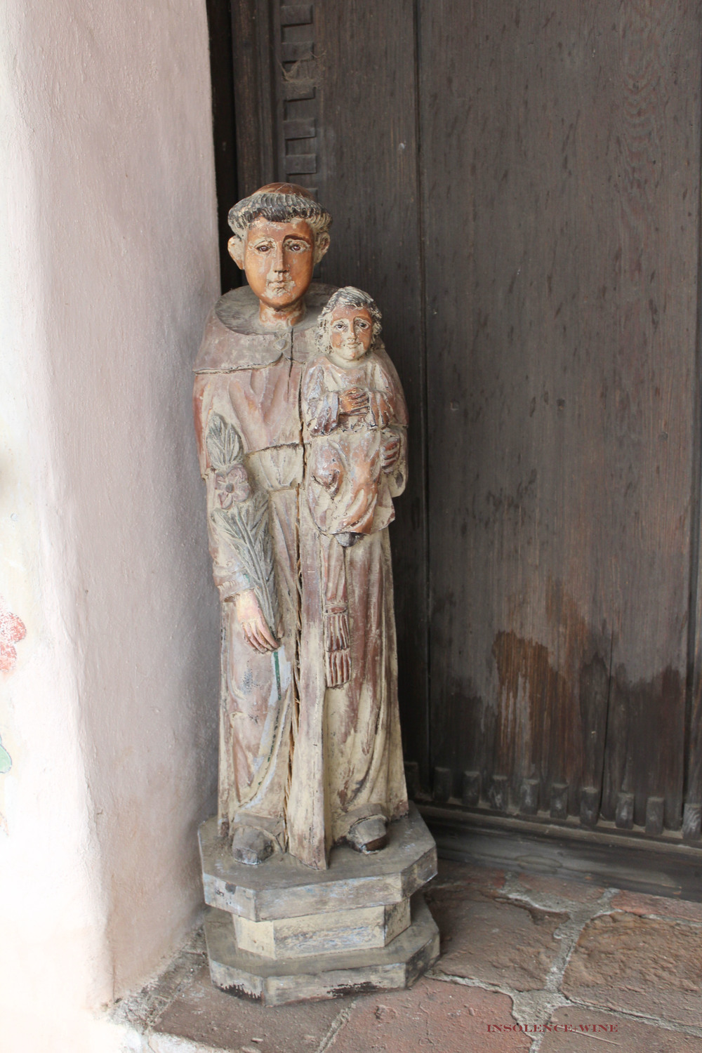 Wooden statuette of St. Anthony de Padua on the steps outside of the church, facing into the courtyard.