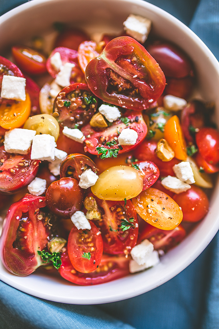 This easy no-cook heirloom tomato salad is loaded with crumbled feta, pistachios and a delicious champagne vinegar drizzle.