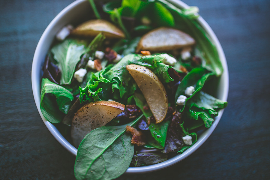 A classic fall salad perfect for Thanksgiving consisting of baby leafy greens, bacon crumble, candied pecans, goat cheese, and asian pears topped off by a delicious vinaigrette. | insolenceandwine.com